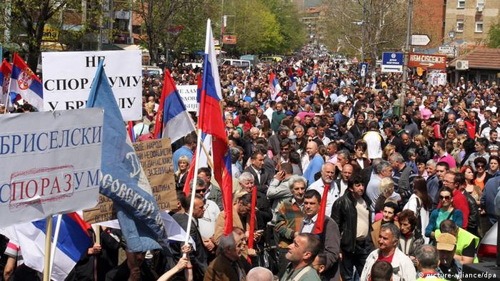 epa03672872 Ethnic Serbs, citizens of Northern Kosovo, wave Serbian national flags and messages against the Brussels Agreement, during a rally that gathered 15,000 people from Northern Kosovo in the ethnically divided city of Mitrovica, Kosovo, Serbia, 22 April 2013. The demonstrators were protesting against an EU-brokered reconciliation agreement between Serbia and Kosovo. The deal is a major prerequisite for Serbia to move closer to EU membership. It is also seen as a first large step toward the normalization of relations between Serbia and its former province, which declared independence in 2008. Belgrade has refused to recognize the mostly ethnic-Albanian entity. Kosovo Serbs, whose autonomy in the north was the toughest sticking point in the negotiations, rejected the agreement in a protest drawing thousands to their hub, the town of Mitrovica. EPA/Djordje Savic