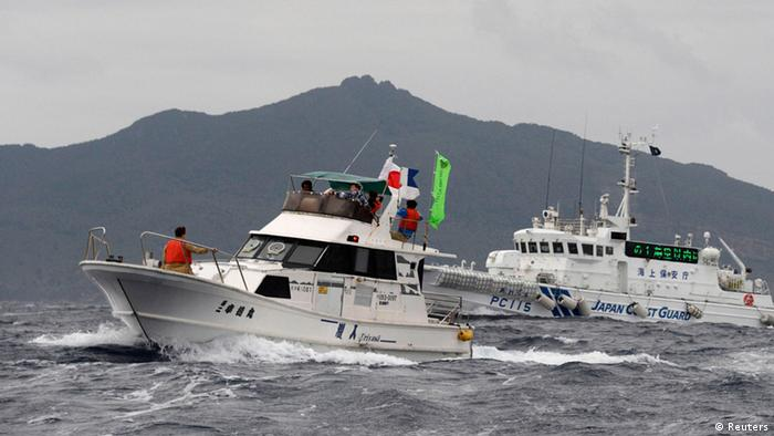 Japan Coast Guard vessel Awagumo (R) approaches a Japanese fishing boat to warn it not to enter waters within one nautical mile from Uotsuri island (background), a part of known as Senkaku isles in Japan and Diaoyu islands in China, in the East China Sea (REUTERS/Kyodo)
