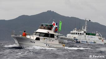 Japan Coast Guard vessel Awagumo (R) approaches a Japanese fishing boat to warn it not to enter waters within one nautical mile from Uotsuri island (background), a part of known as Senkaku isles in Japan and Diaoyu islands in China, in the East China Sea, April 23, 2013 (Photo: REUTERS/Kyodo)