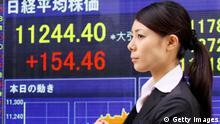 A woman passes before a share prices board in Tokyo on April 1, 2010. Japanese shares closed higher on a Bank of Japan survey indicating a steady improvement of business confidence as the world's second largest economy kicked off a new fiscal year, analysts said. AFP PHOTO / Yoshikazu TSUNO (Photo credit should read YOSHIKAZU TSUNO/AFP/Getty Images)