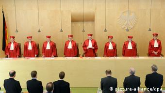 Members of the German Constitutional Court stand, robed in red, in the court house, while a verdict is announced (c) Uli Deck/dpa