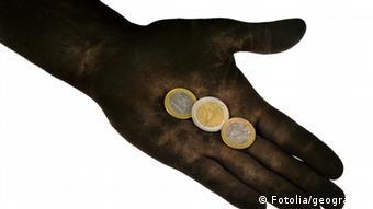 In einer ausgestreckten Hand liegen drei Euro-Münzen