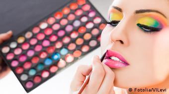 Jemand bemalt die Lippen einer stark geschminkten Frau. In der linken Hand ist ein Schminkkasten mit mehreren Farben