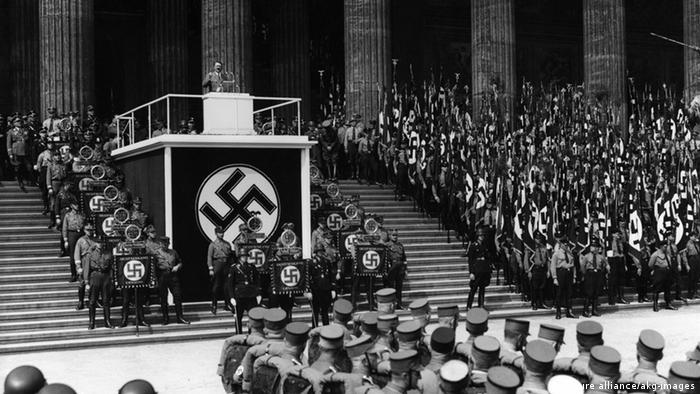 Berlin, 1936. Hitler speaks to crowds from a stage set on stairs, huge swastika