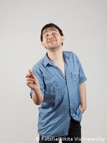 Ein Mann lächelt mit geschlossenen Augen und macht mit den Fingern der rechten Hand das Zeichen für ein bisschen haben