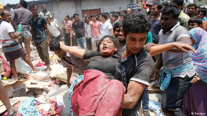 People rescue a garment worker who was trapped under the rubble of the collapsed Rana Plaza building in Savar, 30 km (19 miles) outside Dhaka April 24, 2013. The eight-storey block housing factories and a shopping centre collapsed on the outskirts of the Bangladeshi capital on Wednesday, killing more than 70 people and injuring hundreds, a government official said. (Photo: REUTERS/Andrew Biraj)