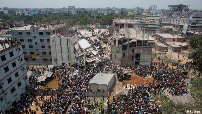 Crowds gather at the collapsed Rana Plaza building as people rescue garment workers trapped in the rubble.