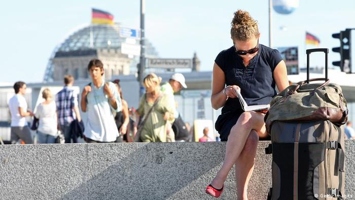 BERLIN, GERMANY - AUGUST 15: A tourist sits next to her suitcase in front of the Reichstag, the seat of the German parliament, on August 15, 2012 in Berlin, Germany. In 2010, nine million tourists visited the German capital, and ten million came in 2011, a new record. Tourism, a major industry for the city since the fall of the Berlin Wall, contributes 9 billion euros (USD 11.1 billion) into the local economy annually, and has a high employment impact, with 230,000 Berliners earning a living in the tourism sector. The increase in visitors is not limited to Berlin; 75 out of 80 German cities reported more tourists in 2011 over the previous year. (Photo by Adam Berry/Getty Images)