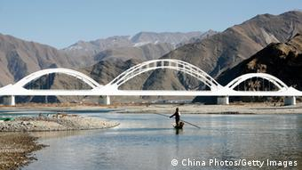 DOILUNGDEQEN COUNTY, CHINA - DECEMBER 18: (CHINA OUT) A man from Sichuan Province fishes in the Brahmaputra River, by the crossing of the Caihong Railway Bridge along the Qinghai-Tibet railway, in the Liuwu Village where the Lhasa Railway Station, a terminal of the Qinghai-Tibet railway, is located on December 18, 2008 in Doilungdeqen County of Tibet Autonomous Region, China. The 1,956km Qinghai-Tibet railway crosses high altitudes to link Xining in Qinghai Province to Lhasa in the Tibet Autonomous Region of China. Employment and wages have been boosted in construction, tourism and service industries in previously remote areas, with decreased transportation costs reducing prices of daily necessities and consumer durables in Tibet. (Photo by China Photos/Getty Images)
