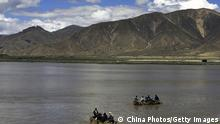 RENBU COUNTY, CHINA - AUGUST 30: (CHINA OUT) Tibetan people row cowskin rafts on the Brahmaputra River on August 30, 2006 in Renbu County of Tibet Autonomous Region, China. Cowskin is a traditional material used to make rafts for fishing and to cross rivers and lakes for the Tibetan peole. (Photo by China Photos/Getty Images)