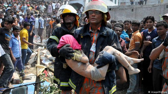 A rescuer carries an injured person after a building collapsed in Savar, Bangladesh, April 24, 2013 (Photo: Xinhua/Shariful Islam)