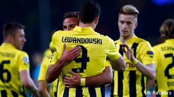 Borussia Dortmund's Robert Lewandowski is congratulated by his team mates after scoring a goal against Real Madrid during their Champions League semi-final first leg soccer match in Dortmund April 24, 2013. REUTERS/Wolfgang Rattay (GERMANY - Tags: SPORT SOCCER)