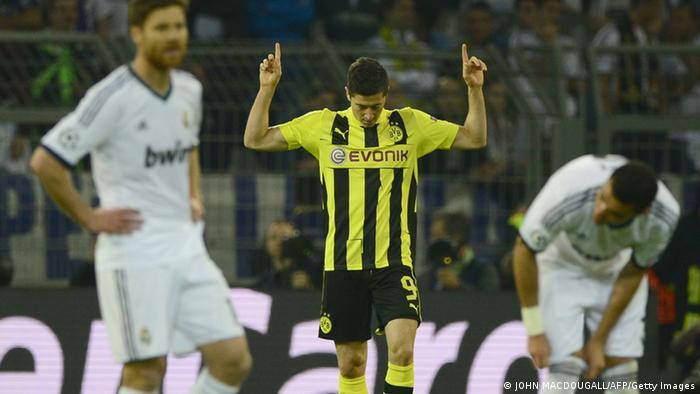 Dortmunds Stürmer Robert Lewandowski hebt jubelnd die Hände, zwei Spieler von Real Madrid schauen enttäuscht (Foto: AFP/Getty Images)