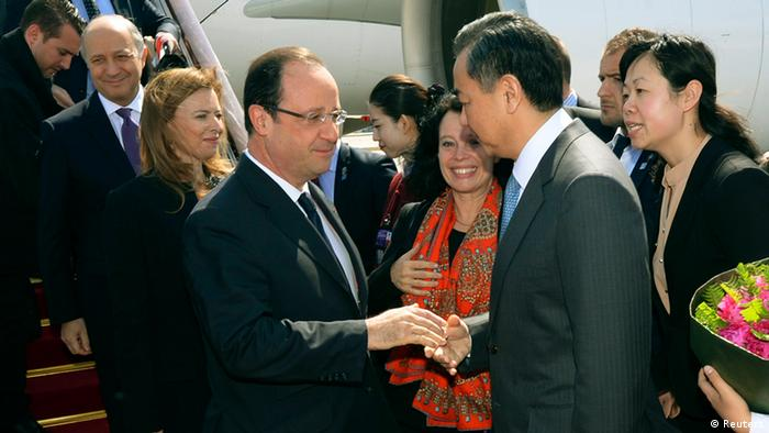 French President Francois Hollande (4th L) and his partner Valerie Trierweiler (3rd L) are greeted by Chinese Foreign Minister Wang Yi (2nd R) as they arrive at the Capital Airport in Beijing (Photo via Reuters)