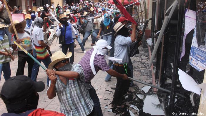 Demonstrators attack the National Action Party's (PAN) headquarters, during riots in Chilpancingo, Guerrero State, Mexico (Photo via dpa)