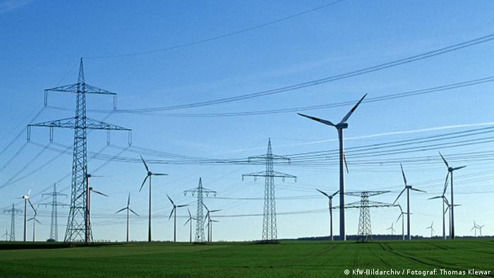 Viele miteinander verbundene Strommasten und Windräder stehen auf einem weiten Feld