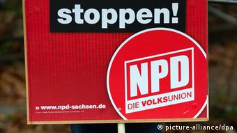 A red sign reads stop and shows the letters NPD in white (Photo: Arno Burgi/dpa)