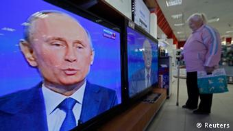 A woman watches televisions broadcasting a nationwide phone-in with Russian President Vladimir Putin (photo: REUTERS/Alexander Demianchuk)