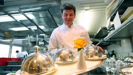 Drei-Sterne-Koch Harald Wohlfahrt posiert mit einem Tablett in der Küche des Restaurants Schwarzwaldstube des Hotels Traube Tonbach in Baiersbronn-Tonbach. Foto: dpa