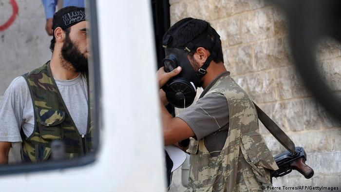 A Syrian opposition fighter tries a gasmask in the northern city of Aleppo on July 25, 2012. Battles raged through the night in several districts of Syria's second largest city to which the regime had rushed reinforcement, after rebels launched an all-out assault for control of the country's commercial hub on July 20. Arabic graffiti on the police station's entrance reads Assad's Syria. AFP PHOTO / PIERRE TORRES (Photo credit should read Pierre Torres/AFP/GettyImages)