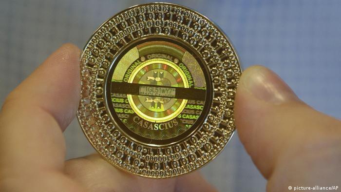 Bitcoin held by two fingers (picture-alliance/AP)