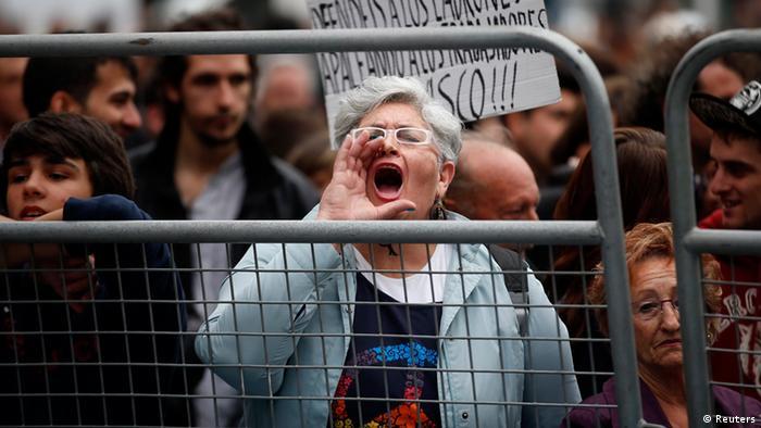 Демонстрация протеста в Мадриде против мер экономии: женщина из-за ограждения выкрикивает лозунги
