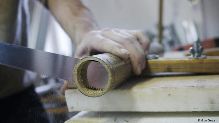 A man cutting through bamboo (Photo: Guy Degen)