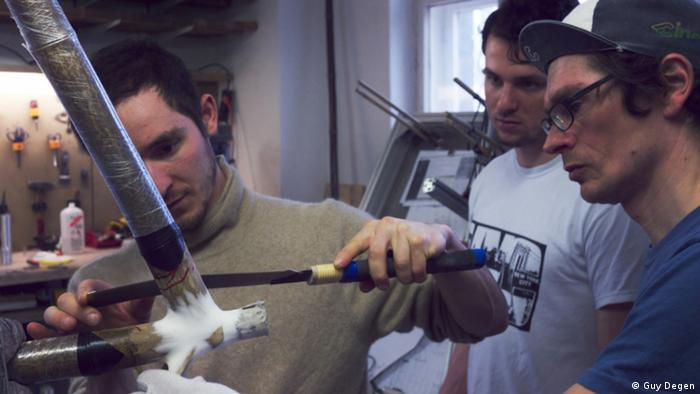 Designer Dan Vogel-Essex (left) showing workshop participants how to shape their bamboo frame (Photo: Guy Degen)
