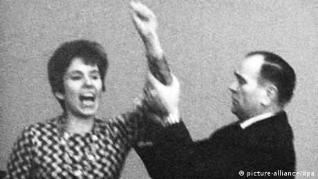 Beate Klarsfeld holding up her arm, and being restrained.