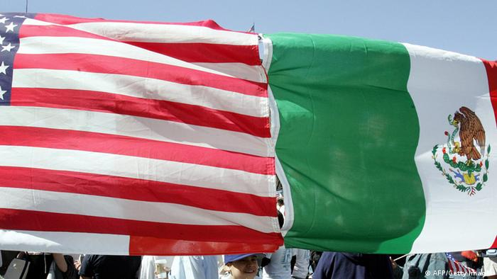 Protesters hold an American and Mexican flag that has been stitched together 