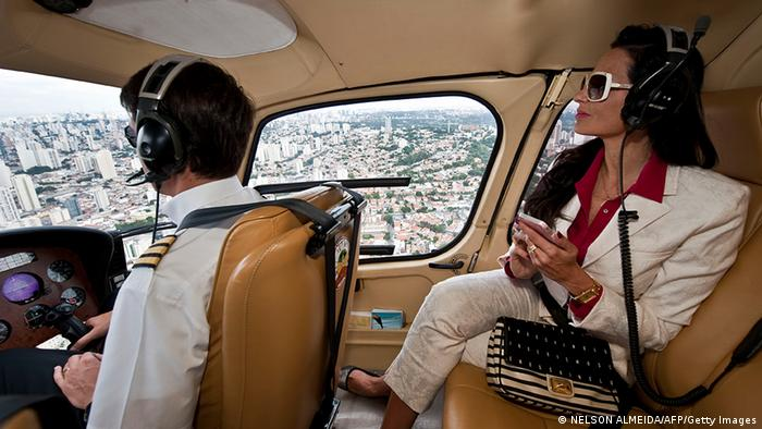 Brazilian millionaire Cozete Gomes (R) checks her cellphone as she flies on her helicopter over Sao Paulo, on April 4, 2013. (Photo: NELSON ALMEIDA/AFP/Getty Images)
