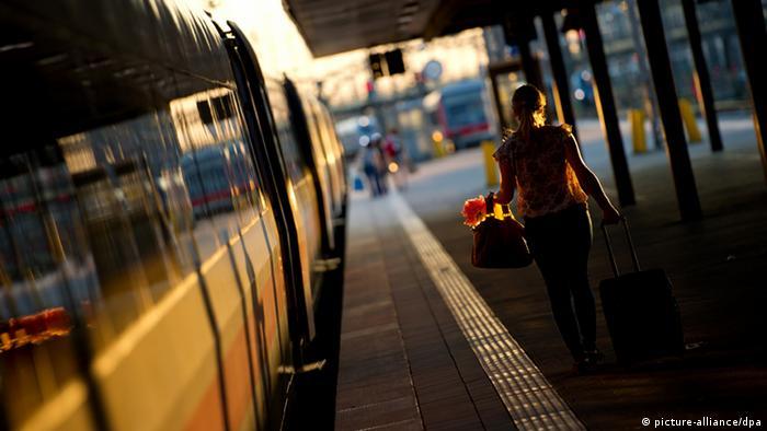 Eine Frau geht während des Sonnenuntergangs über einen einsamen Bahnsteig