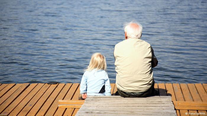 Großvater und Enkelkind sitzen auf einem Steg am Wasser