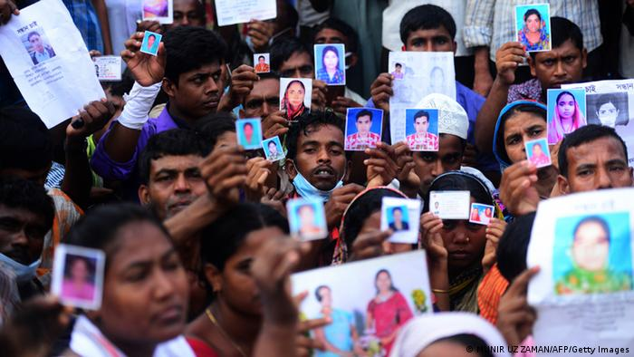 Bangladeshi relatives hold photos of the missing and dead workers three days after an eight-storey building collapsed in Savar, on the outskirts of Dhaka on April 27, 2013. Police arrested two textile bosses over a Bangladeshi factory disaster as the death toll climbed to 332 and distraught relatives lashed out at rescuers trying to detect signs of life. AFP PHOTO/ Munir uz ZAMAN (Photo credit should read MUNIR UZ ZAMAN/AFP/Getty Images)