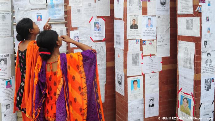 Two Bangladeshi women look at a board with notices posted of missing and dead workers three days after an eight-storey building collapsed in Savar, on the outskirts of Dhaka, on April 27, 2013. Police arrested two textile bosses over a Bangladeshi factory disaster as the death toll climbed to 332 and distraught relatives lashed out at rescuers trying to detect signs of life. AFP PHOTO/ Munir uz ZAMAN (Photo credit should read MUNIR UZ ZAMAN/AFP/Getty Images)