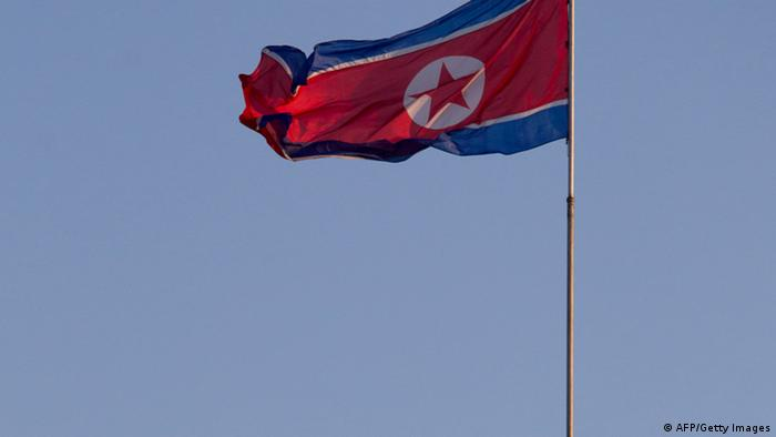 A soldier stands beneath a North Korean flag prior to celebrations to mark the 100th birth anniversary of the country's founding leader Kim Il-Sung, in Pyongyang on April 16, 2012. The commemorations came just three days after a satellite launch timed to mark the centenary fizzled out embarrassingly when the rocket apparently exploded within minutes of blastoff and plunged into the sea. AFP PHOTO / Ed Jones (Photo credit should read Ed Jones/AFP/Getty Images)