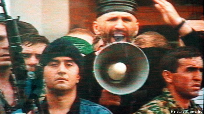 An image taken from the Russian TV news showing an unidentified Moslem activist speaking over a megaphone while heavily armed men stand next to him downtown Makhachkala, capital of the Russian Caucasus republic of Dagestan, 21 May. Hundreds of gunmen loyal to the top Russian Moslem leader Magomet Khachilayev and his brother Nadirshah clashed with police and seized the government building in Makhachkala. dpa