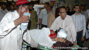 Pakistani men wheel an injured blast victim on a stretcher in a hospital following a bomb explosion in Karachi on April 27, 2013 (Photo: ASIF HASSAN/AFP/Getty Images)