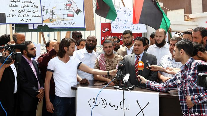 Member of the Supreme Council of Libyan Revolutionaries Adel al Ghiryani (R) adresses to journalists in front of the foreign ministry that has been surrounded by gunmen demanding it be cleansed of agents and ambassadors of ousted dictator Moamer Kadhafi on April 28(Photo: MAHMUD TURKIA/AFP/Getty Images)
