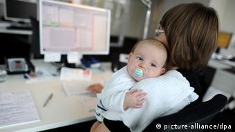 Eine junge Mutter sitzt mit ihrem Baby an ihrem Schreibtisch, auf dem der Monitor eines Computers steht. (Foto: Tim Brakemeier / picture alliance / dpa)