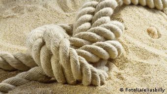 Ein dickes Seil mit einem Knoten liegt im Sand
