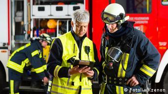 Drei Feuerwehrleute. Die beiden im Vordergrund besprechen etwas