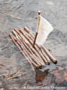 Ein kleines Holzfloß mit einem kleinen Segel im Wasser