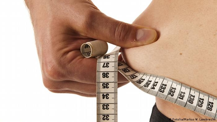 Person measuring and pinching waist (Fotolia/Markus W. Lambrecht)