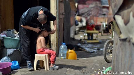 A man cuts the hair of a young boy sat on a chair in a Roma settlement of Belvil in Belgrad, Serbia. Photo: Britta Pedersen/dpa +++(c) dpa - Bildfunk+++
