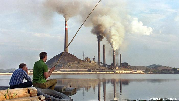 Two Russian men fish in a lake across from a factory