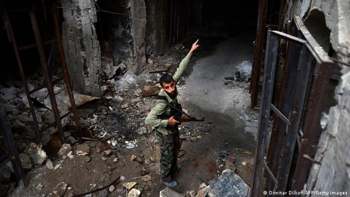 A bearded man in battle dress uniform points with his free hand into the destroyed rubble of a stone mosque while holding an AK-47 rifle in the other (Photo:DIMITAR DILKOFF/AFP/Getty Images)