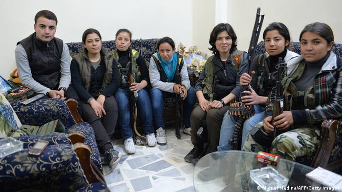 Kurdish female fighter Engizek (2nd L), who leads dozens of Kurdish combatants, sits with her comrades inside a house in the majority-Kurdish Sheikh Maqsud district of the northern Syrian city of Aleppo, on April 21, 2013. A short, diminutive woman flanked by gun-toting loyalists, Engizek leads dozens of Kurdish combatants in Aleppo city's embattled district of Sheikh Maqsud, large parts of which were seized late last month from regime fighters. AFP PHOTO/MIGUEL MEDINA (Photo credit should read MIGUEL MEDINA/AFP/Getty Images)