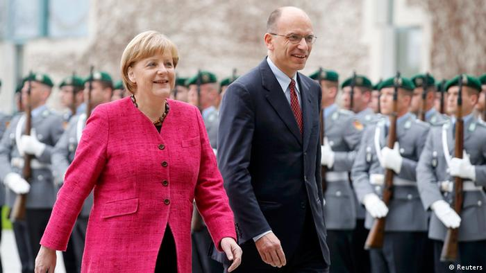 German Chancellor Angela Merkel and Italian Prime Minister Enrico Letta inspect a guard of honour during a welcome ceremony outside the Chancellery in Berlin, April 30, 2013. REUTERS/Tobias Schwarz (GERMANY - Tags: POLITICS)