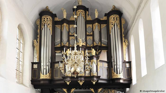 A church organ made of metal and wood painted black.